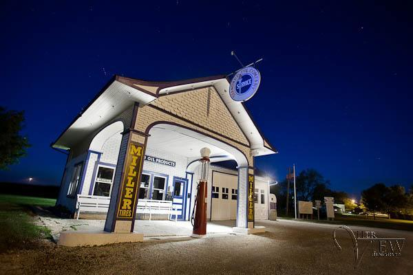 a historic gas station is lit with light for a night photography