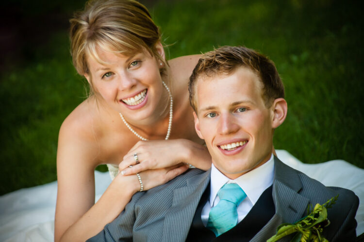 A classic wedding photo portrait of bride and groom using a 150mm long lens gives a soft background where the people are featured