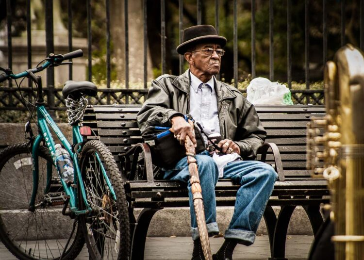 with long camera lenses, it's possible to photography people from a distance without them knowing, like this image of a man on a bench in New Orleans