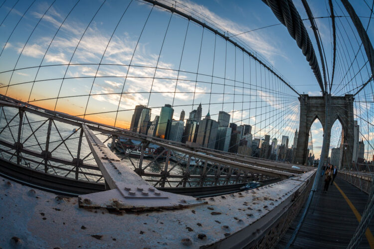 a wide angle lens makes this photo of new york city bridge look distorted and the city smaller