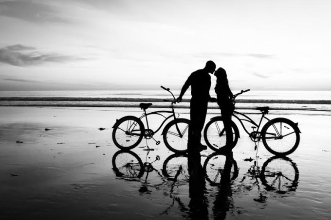 Silhouette picture of a young couple kissing on beach with bicycles
