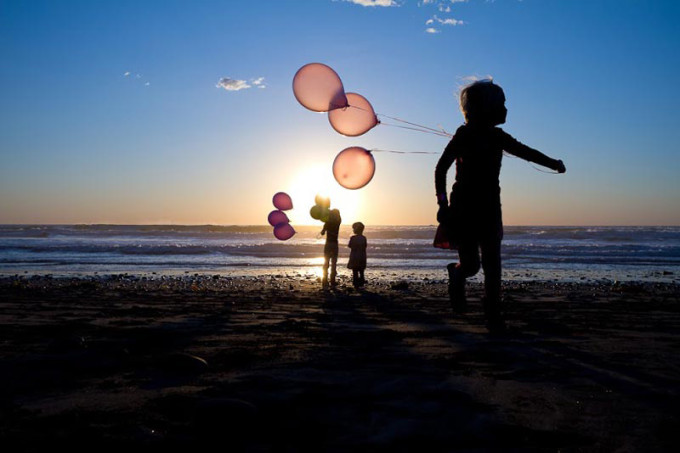 children with balloons in silhouette