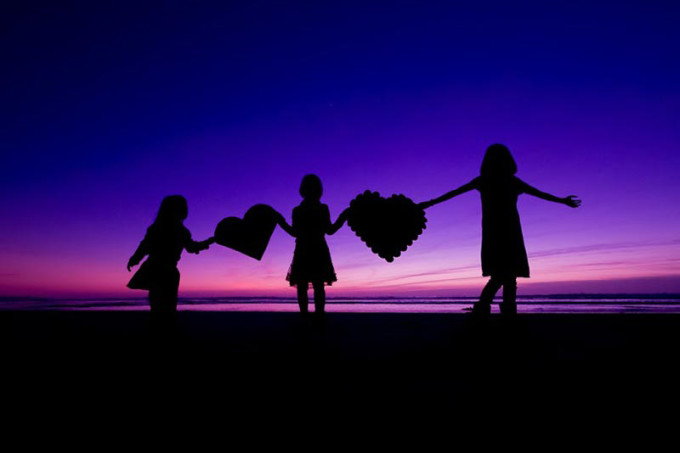 silhouette picture of children on a beach with hearts