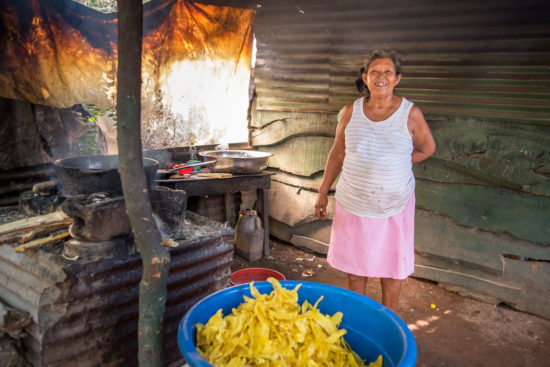 woman poses next to a batch of fried plantains inside her house