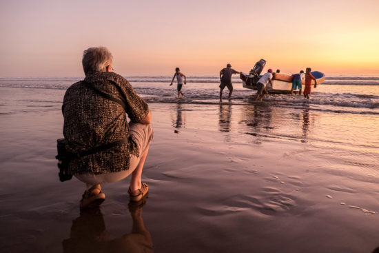 photographer capturing photos of fishermen as they come in at sunrise