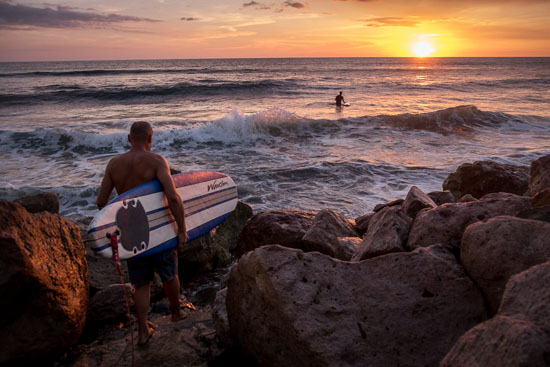 surfer heads out at sunset