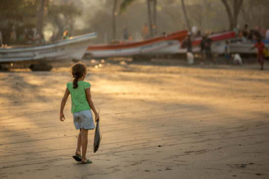 young girl with fish walks along beach of the fishing village