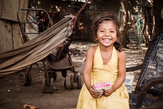 young nicaraguan girl poses in her yellow dress