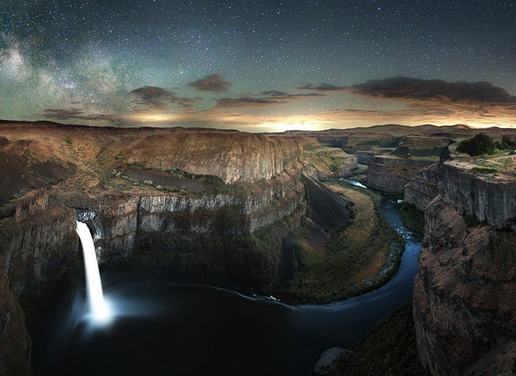 Long exposure photograph of a waterfall with the night sky as a backdrop