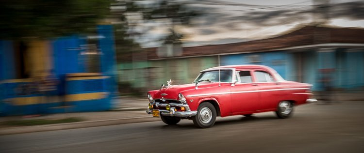 a slower shutter speed along with panning technique creates this blurred photo of a classic car in Havana Cuba