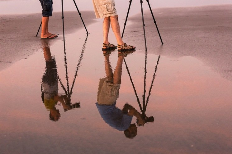 Reflection of two photographers using tripods on the beach