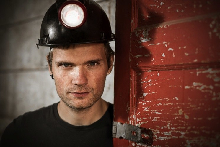 85mm portrait lens example image, a young miner with safety helmet
