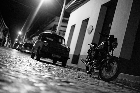 a car and a motorcycle on the cobblestone street at night