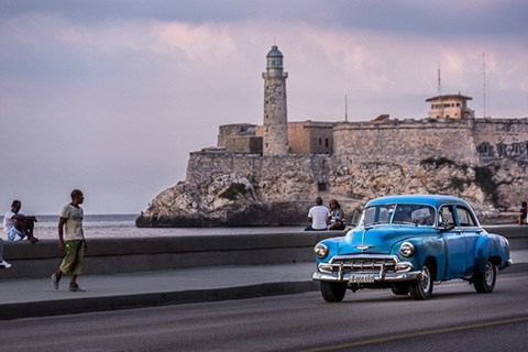 a classic car drives by on the Malecon