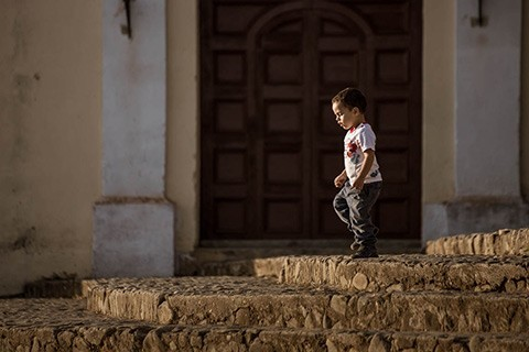 little boy in Trinidad Cuba walks down stone steps with the sun on his face