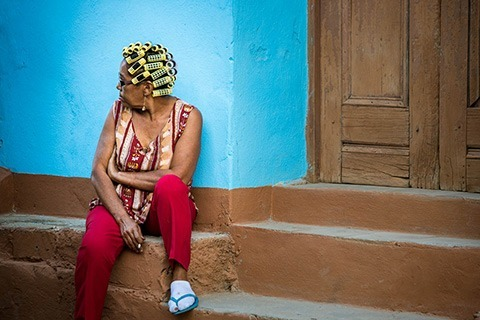 woman in curlers sits on the curb in Trinidad, Cuba