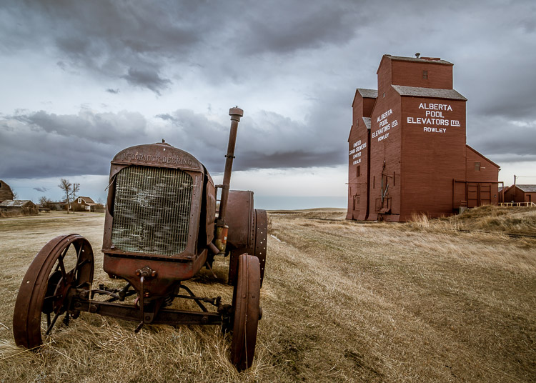 a wide angle lens adds depth and makes the old tractor look good with the grain elevators in the background