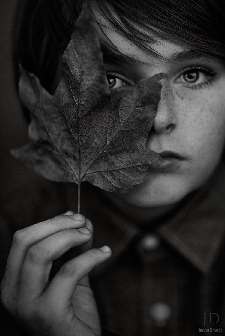black and white portrait of a small boy holding a leaf in front of his face