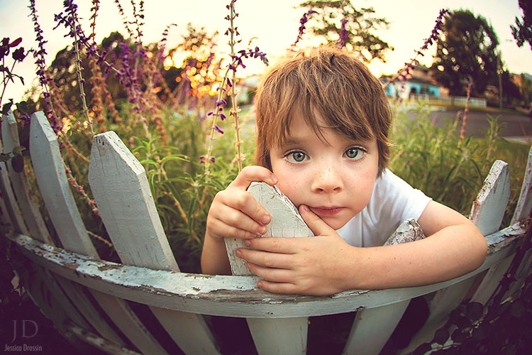 close up photo with a wide angle lens of my kid leaning on a white picket fence