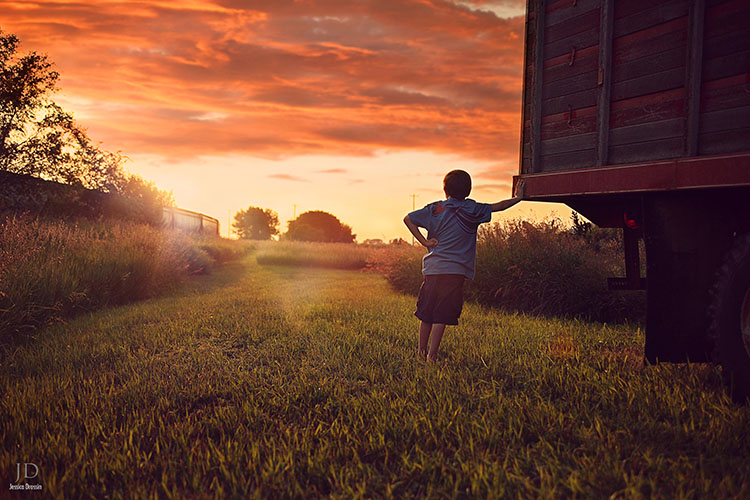 photo of a kid in the field next to a truck watching the sunset