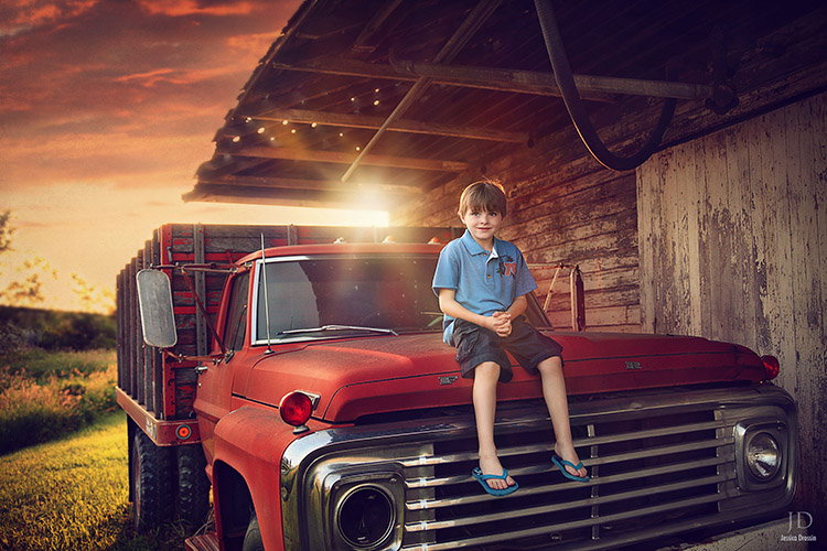 family photograph of my kid on an old truck with the sun setting behind him