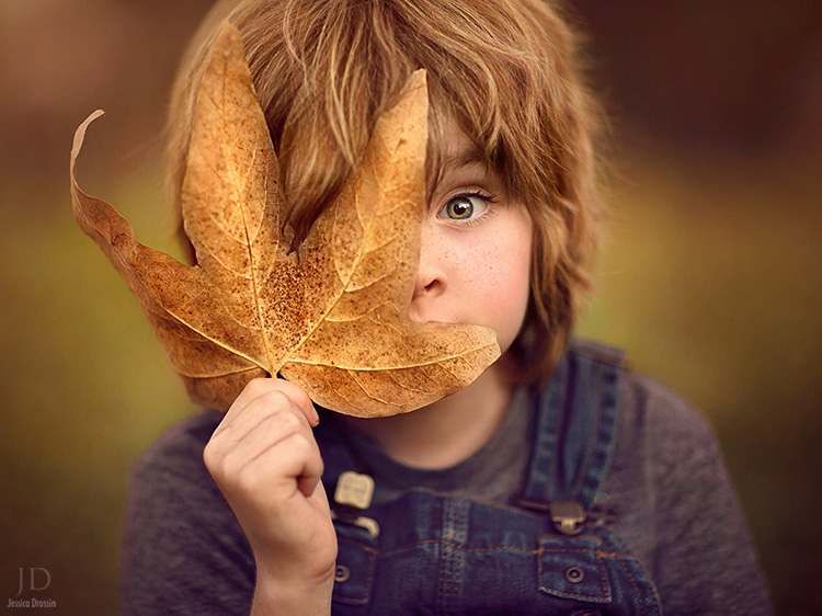 color photo of a child and a big leaf