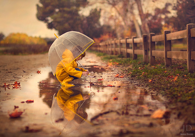 kid plays with a fallen leaf in a puddle after a rain storm.