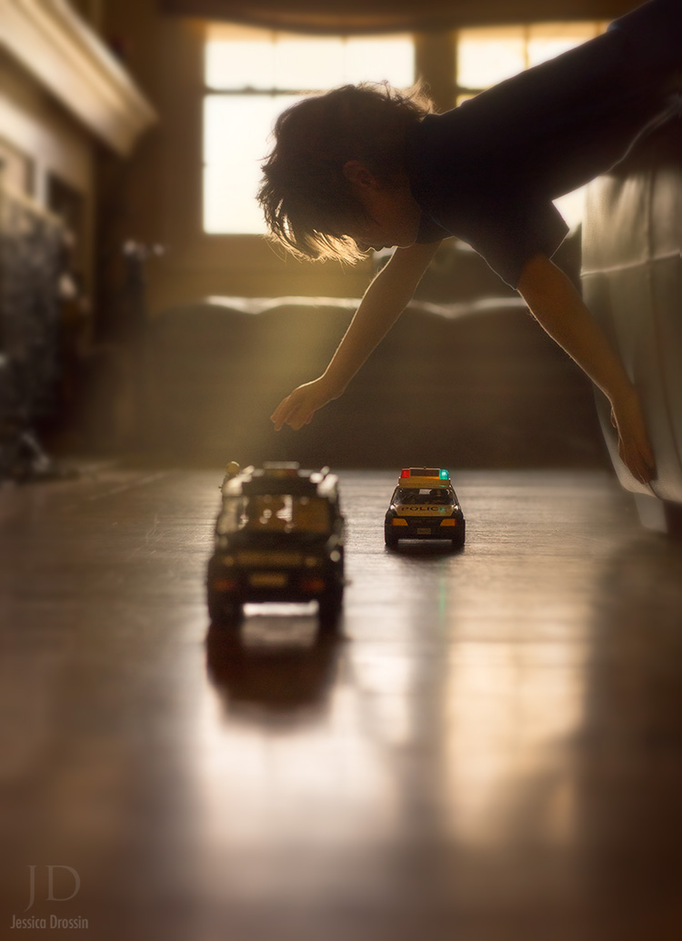 a young boy leans over the bed and plays with his toy cars on the floor