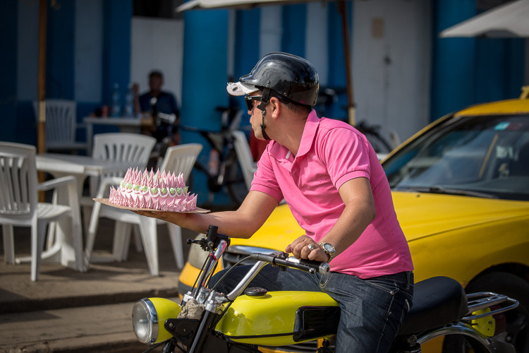 Street photograph of a man on a motorbike with a cake in Vinales Cuba