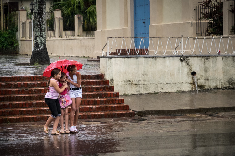 Street photograph of 3 girls in the rain in Vinales Cuba