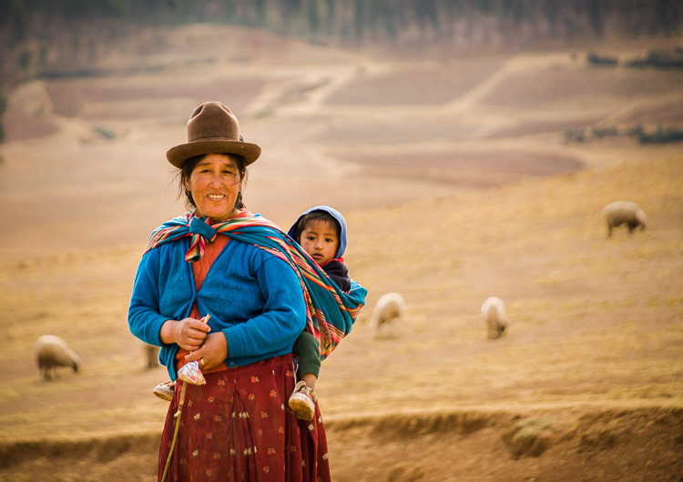 Ladies walking in a field with food for their husbands in Peru