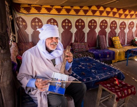 a berber musician plays his instrument in a tent