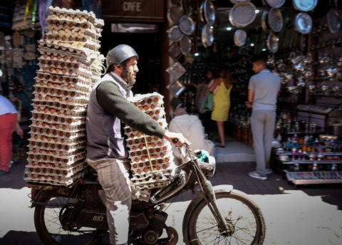 a motorcycle is loaded up with stacks of eggs for delivery