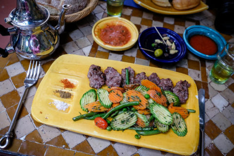 a plate of traditional Morrocan food.  Olives, meat, carrots and cucumber
