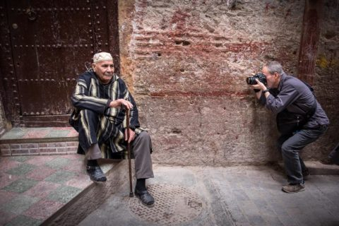 a tour participant captures the portrait of a local man as he sits on the step