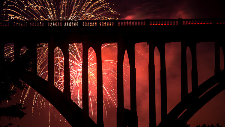 Bridge silhouette captured with red glow from fireworks exploding behind it by zooming in tigher
