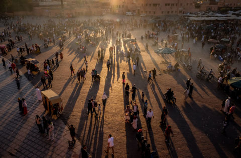 people in the marakesh market create long shadows