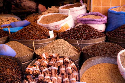 bowls of spices and herbs on display at the market