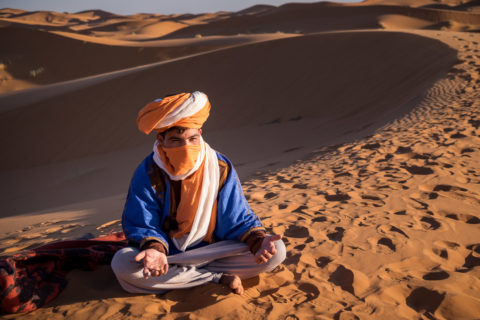 berber man sits on the sand in the saraha desert