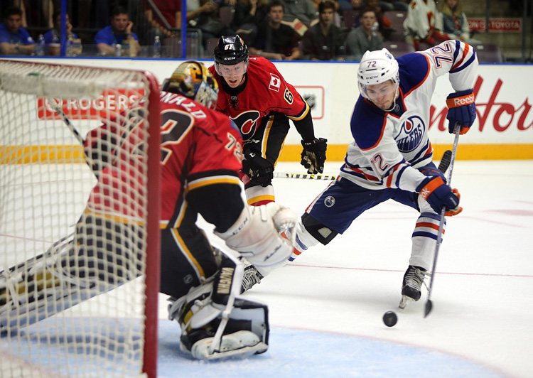 an Edmonton Oiler goes in on the net against Calgary Flames goal tender