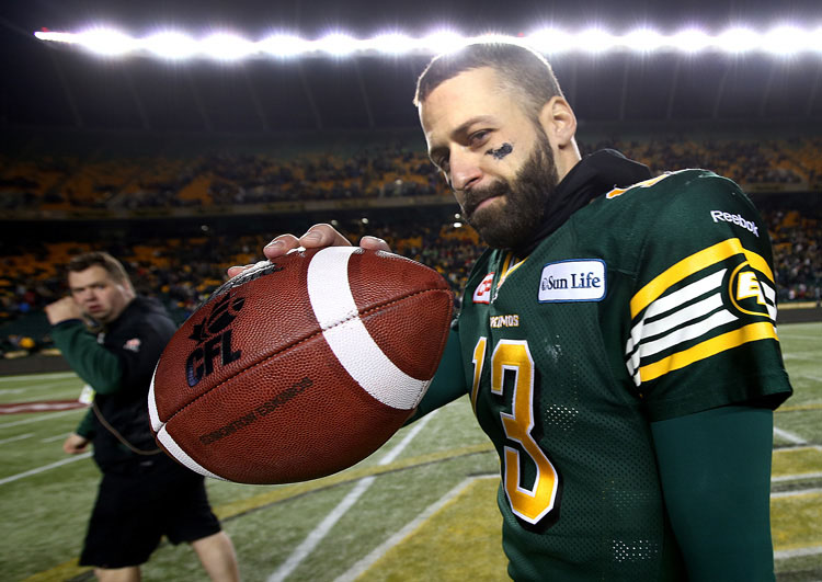 Edmonton Eskimo football player showing the ball to photographer