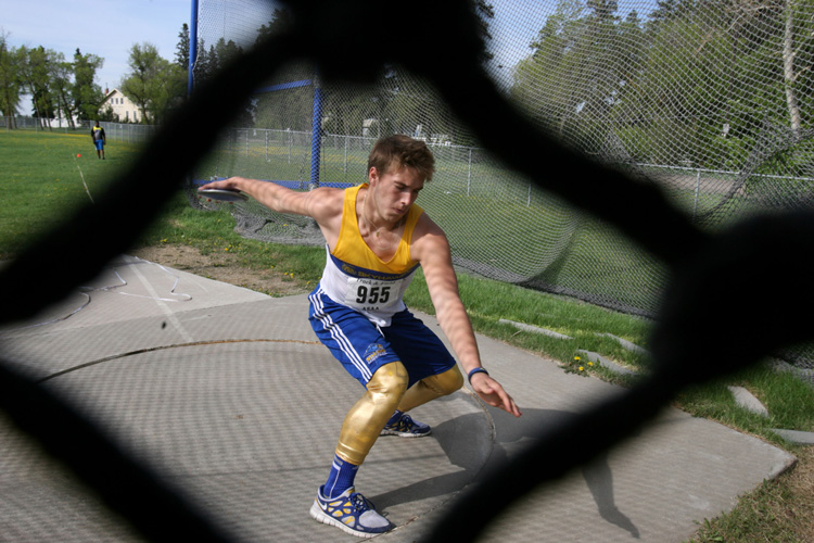 Discus athlete photographed from behind a fence providing a unique angle