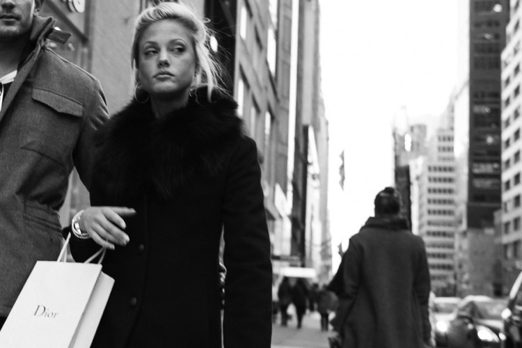 Black and white photo of woman carrying a Dior bag on the streets of New York