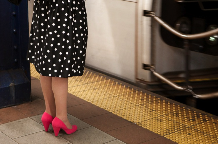 Street photo of a woman wearing a polka dot dress and pink shoes