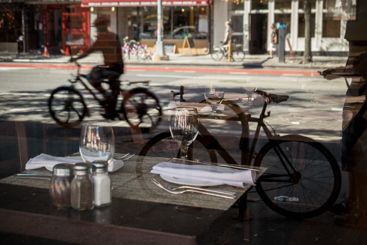 I saw the parked bike reflected in the cafe window and was able to position myself to see the table inside and the bike. My first shot felt empty though so I waited for cyclist to pass by and timed my shot to capture him too. It took me about six tries to get this one - patience is a virtue in photography!