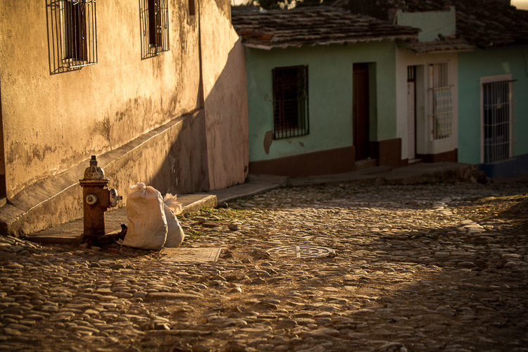 This is a spot I found at sunset in Trinidad Cuba. It's got gorgeous light, sweeping across the cobble stones. It just felt a bit empty to me. So I waited.