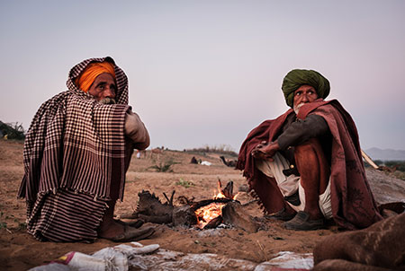 Camel herders by a fire pit early morning in the Pushkar Camel Fair grounds.