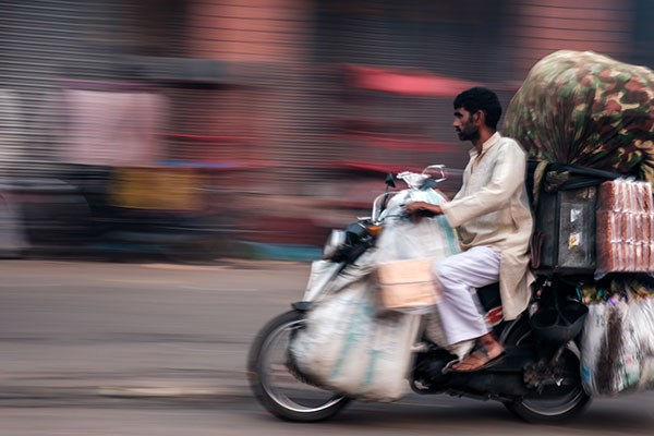 Man on motorbike in the streets of Delhi India, carrying goods.