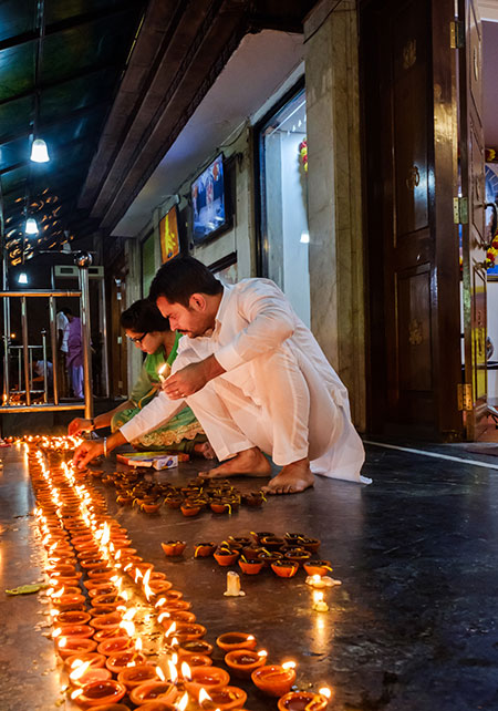Couple lighting candles for the Diwali celebration at the Sai Baba Temple in the Hauz Khas area of New Delhi
