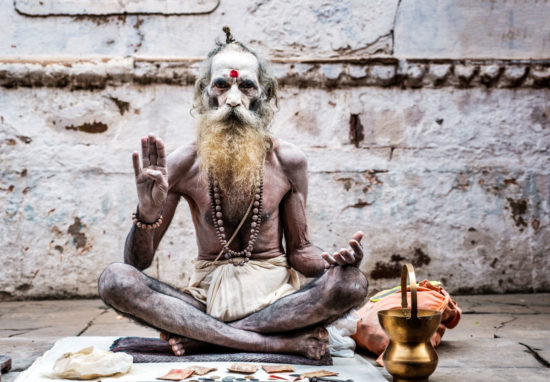 Indian man with face painted sits cross legged